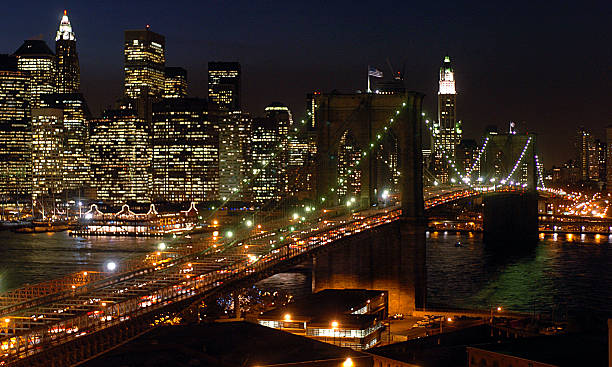 A well-lighted Brooklyn Bridge, spanning the East River, is