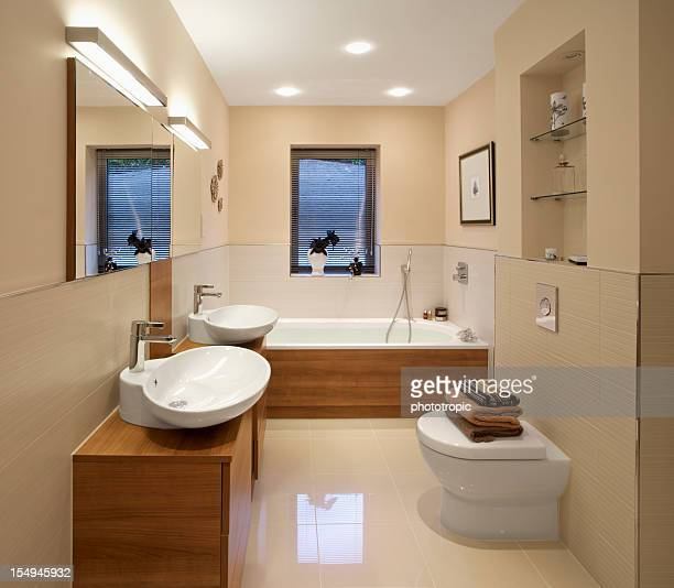 Well-lit luxurious bathroom with double vanity and tub