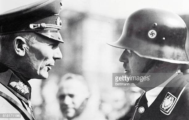 Wellprotected by a steel helmet Herr Heinrich Himmler the German Chief of Police Head of the Gestapo and commander of the SS Nazi Guards talking with...