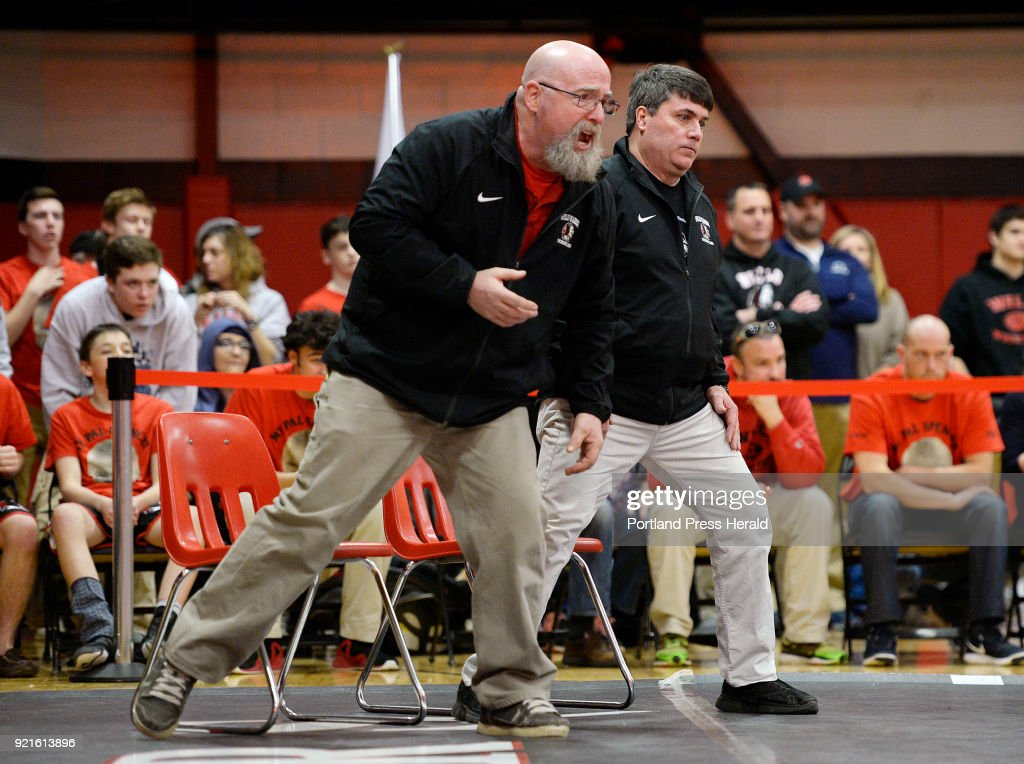 Wells coaches Jim Worthing, left, and head coach Scott Lewia cheer on Wells wrester Michael Wrigley during the Class B state wrestling championships at Wells High Saturday, February 17, 2018.