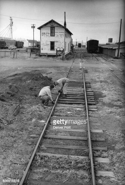 Wells left and Glazier measure a broken rail near Center White building to the left of tracks used to be office headquarters for the railroad Credit...
