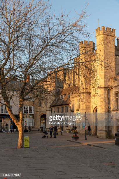 Wells Somerset England UK Glowing sun illuminates the Market Place and Bishops Eye Gatehouse and Penniless Porch in the cathedral city in the Mendip...