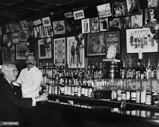 A wellstocked bar at Bill's Gay Nineties a speakeasy located at 57 East 54th Street New York City circa 1940 The barman is wearing a large fake...