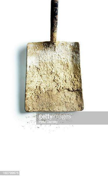 A well-used spade covered in cement dust