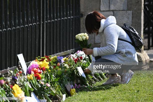 Well-wisher adds flowers to tributes outside Windsor Castle in Windsor, west of London, on April 11 two days after the death of Britain's Prince...