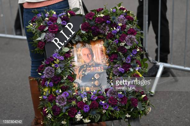Well-wisher arrives to deliver a floral tribute to Windsor Castle in Windsor, west of London, on April 14 following the April 9 death of Britain's...