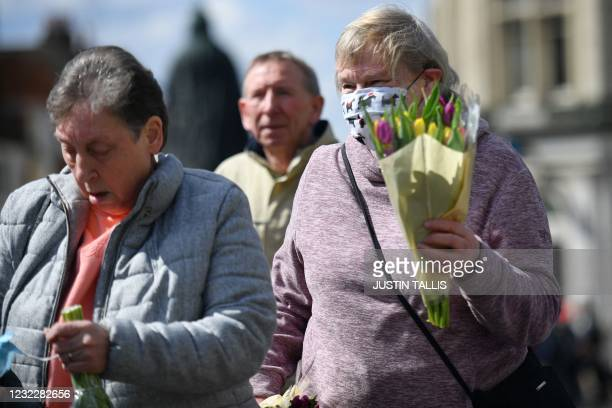 Well-wisher carries floral tributes outside Windsor Castle in Windsor, west of London, on April 13 following the April 9 death of Britain's Prince...