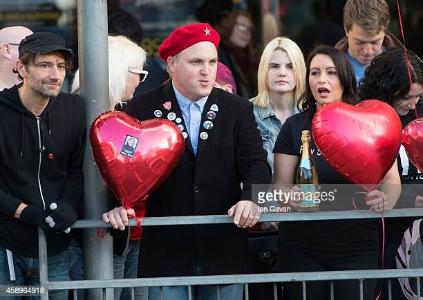 A wellwisher dressed as Vivien from 'The Young Ones' looks on as a memorial bench for the late Rik Mayall is unveiled on November 14 2014 in London...
