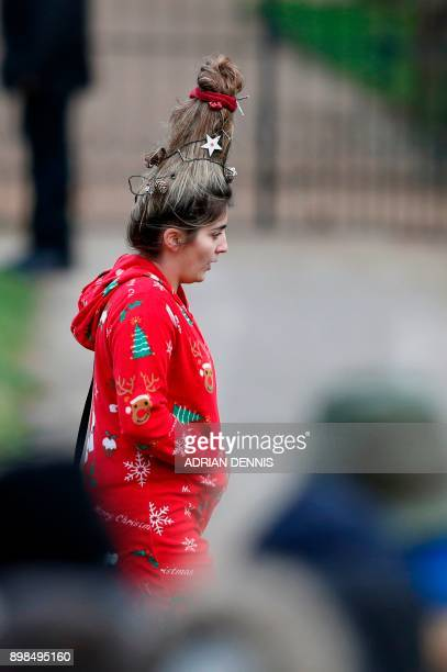 Well-wisher dressed in a Christmas outfit arrives to greet members of the Royal Family arriving for the traditional Christmas Day church service at...