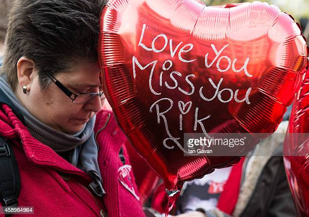 A wellwisher hold balloons as a memorial bench for the late Rik Mayall is unveiled on November 14 2014 in London England