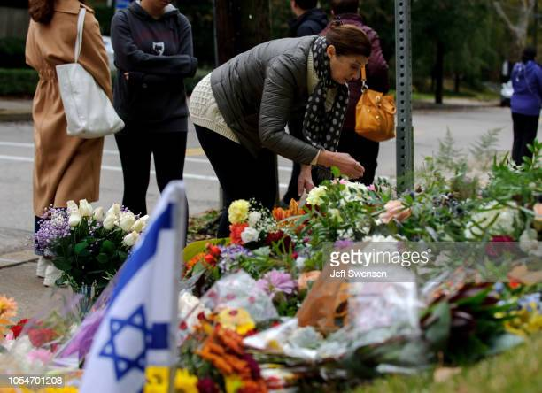 A wellwisher lays a bouquet of flowers at a makeshift memorial down the street from the site of the mass shooting that killed 11 people and wounded 6...