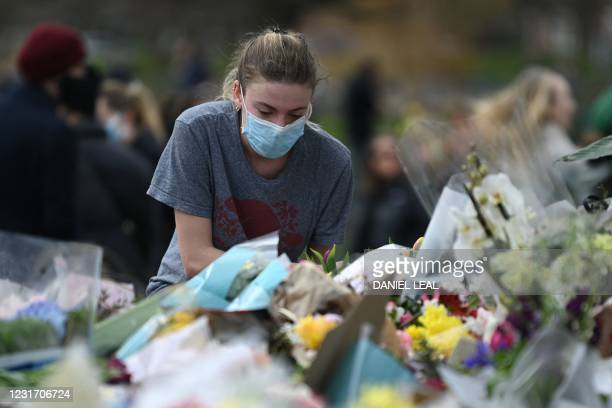 Well-wisher pauses at floral tributes to honour alleged murder victim Sarah Everard at the bandstand on Clapham Common in south London on March 14 a...