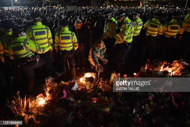 Well-wisher places a adds a tribute to the growing pile from a gap in a police cordon at the band-stand where a planned vigil in honour of alleged...