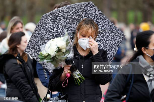 Well-wisher waits in line to lay a floral tribute to Britain's Prince Philip, Duke of Edinburgh outside Buckingham Palace, central London on April 10...