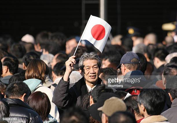 Wellwisher waves a Japanese national flag to cerebrate Japanese Emperor Akihito's 73rd birthday at the Imperial Palace in Tokyo Japan on Saturday...