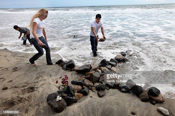 Wellwishers Adam Alvarado Ashley Priest and Jimmy Garcia create a cross made out of stones across the street from Junior Seau's beach home May 2 2012...