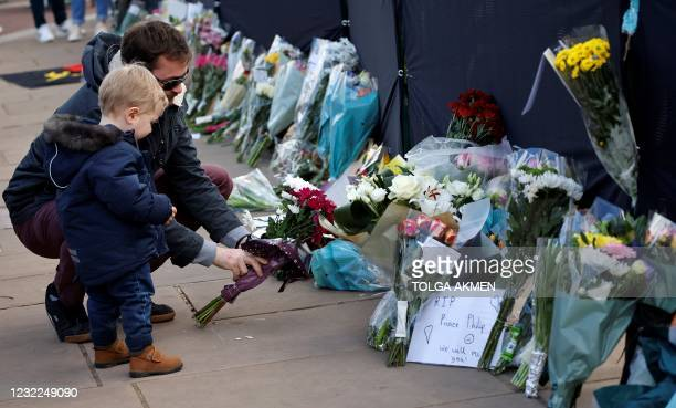 Well-wishers add flowers to the tributes outside Buckingham Palace in central London, on April 11 two days after the death of Britain's Prince...