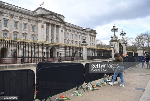 Well-wishers add flowers to the tributes outside Buckingham Palace in central London, on April 15 following the April 9 death of Britain's Prince...