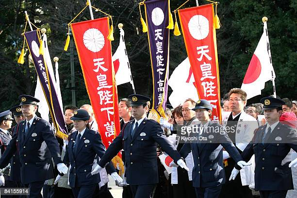 Wellwishers are restrained by police as they enter the Imperial Palace to cheer Emperor Akihito and celebrate the New Year at the Imperial Palace on...