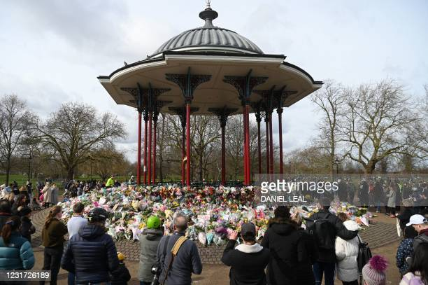 Well-wishers gather beside floral tributes to honour alleged murder victim Sarah Everard at the bandstand on Clapham Common in south London on March...