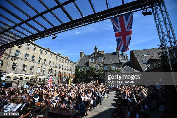 Wellwishers gather to watch the Royal Wedding of Britain's Prince Harry Duke of Sussex and US actress Meghan Markle on a big screen at the Pear Tree...