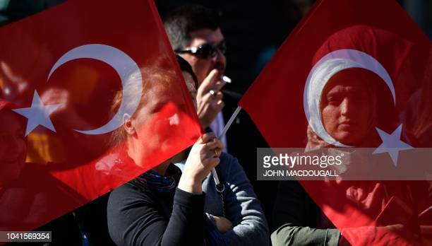 Wellwishers hold Turkish flags near the Adlon Hotel close to the Brandenburg Gate in Berlin where preparations are under way for a state visit of the...