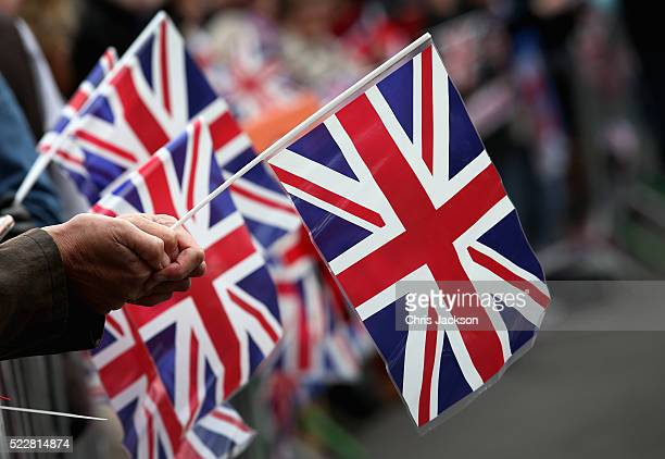 Wellwishers hold Union Jack flags gather for the Queen's 90th Birthday Walkabout on April 21 2016 in Windsor England Today is Queen Elizabeth II's...