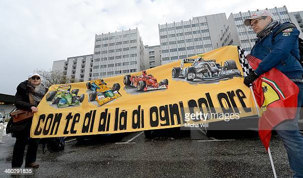 Wellwishers hold up a banner displaying the various racing teams for which Michael Schumacher drove and the message With You No Matter Which Color as...