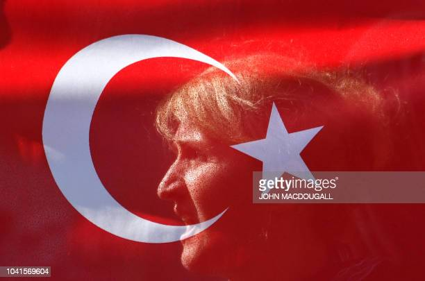 TOPSHOT A wellwishers is seen behind a Turkish flag near the Adlon Hotel close to the Brandenburg Gate in Berlin where preparations are under way for...