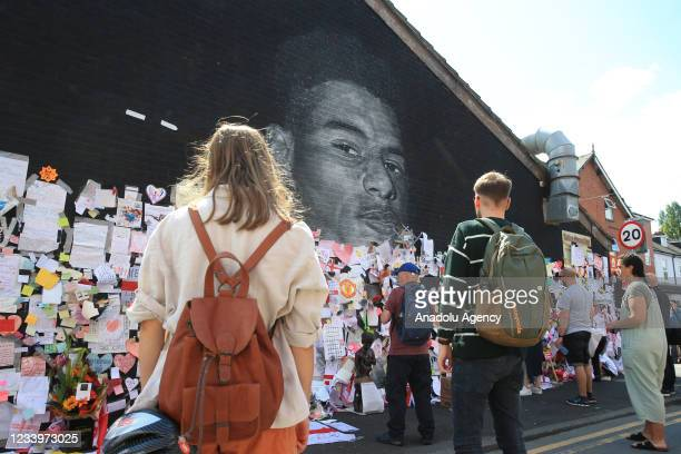 Well-wishers leave messages of support at a mural of British footballer Marcus Rashford in his hometown of Withington in Manchester, north west...