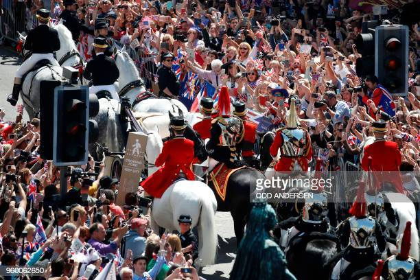 Wellwishers lining the streets wave and cheer as Britain's Prince Harry Duke of Sussex and his wife Meghan Duchess of Sussex pass riding in the Ascot...
