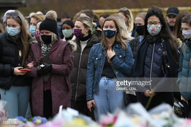 Well-wishers react as they gather at floral tributes to honour alleged murder victim Sarah Everard at the bandstand on Clapham Common in south London...