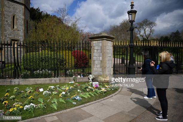 Well-wishers reflect near messages and floral tributes outside Windsor Castle in Windsor, west of London, on April 13 following the April 9 death of...