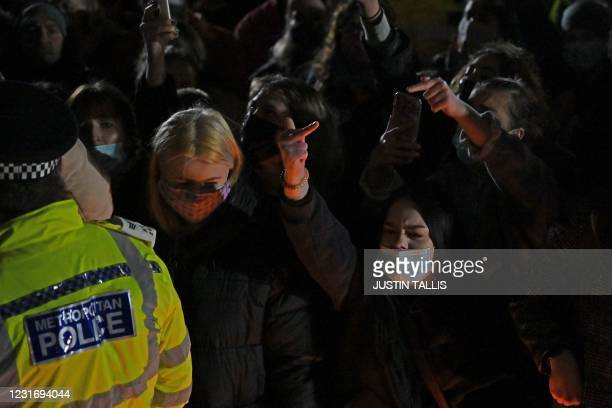 Well-wishers shout and gesture at police at the band-stand where a planned vigil in honour of alleged murder victim Sarah Everard, which was...