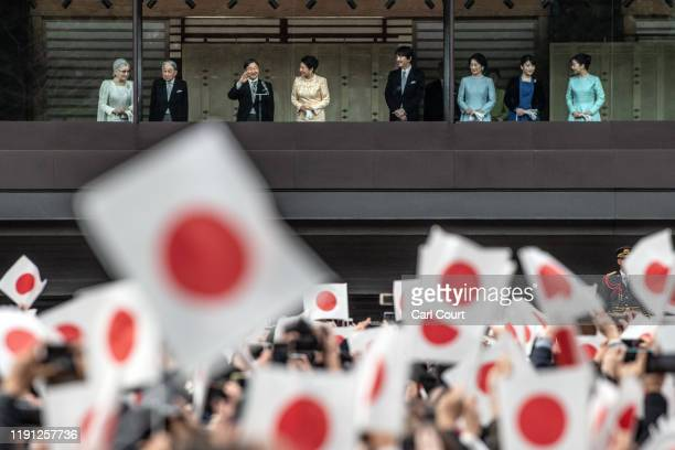Wellwishers wave flags as Emperor Naruhito of Japan waves after delivering a traditional New Year's greeting at the Imperial Palace on January 2 2020...