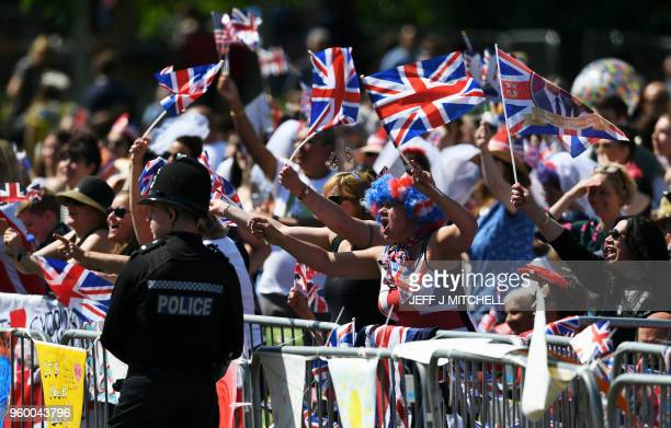 Well-wishers wave flags on the Long Walk leading to Windsor Castle ahead of the wedding and carriage procession of Britain's Prince Harry, Duke of...