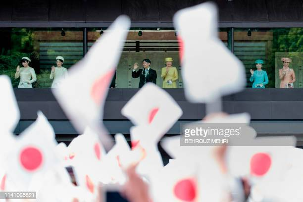 Wellwishers wave Japanese flags as Japan's Emperor Naruhito and Empress Masako make their first public appearance after ascending to the throne along...