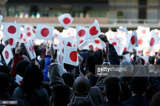 Wellwishers wave national flags and make banzai cheers during a celebration for the New Year by the Japanese Royal Family on the veranda of the...