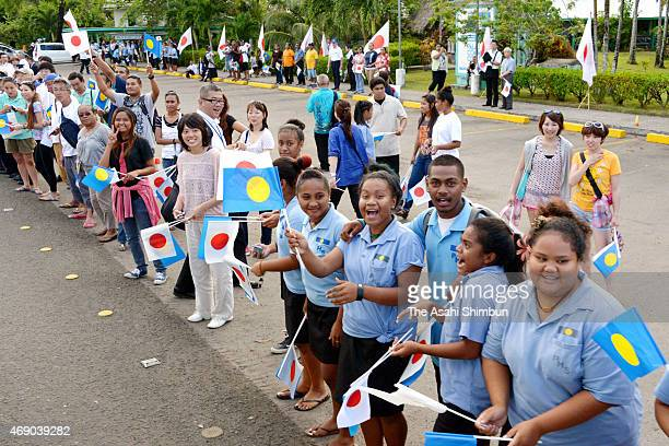 Wellwishers wave national flags of Japan and Palau as they wait for Emperor Akihito and Empress Michiko at the Palau International Airport on April 8...