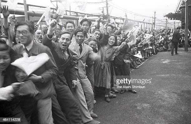 Well-wishers wave the national flags to Emperor Hirohito at the Japan Iron and Steel Yahata Steel Yard during his visit to Kyushu on May 19, 1949 in...