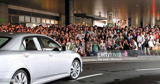 Wellwishers wave toward a car carrying Crown Prince Naruhito and Crown Princess Masako at JR Sendai Station to evacuees of 2011 Great East Japan...