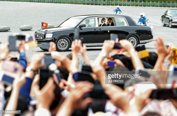 Wellwishers wave towards Japan's new Emperor Naruhito as he leaves in a vehicle from the Imperial Palace after ceremonies for the accession to the...