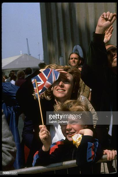 Wellwishers waving British flags as they bid farewell to troops sailing on QE2 as it departs for Falkland Isands