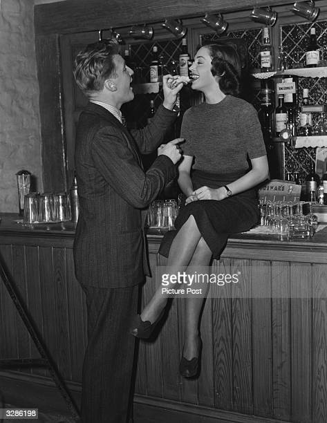 Welsh actor Donald Houston feeds actress Natasha Parry a titbit in a scene from the film 'Dance Hall' an Ealing studios production directed by...