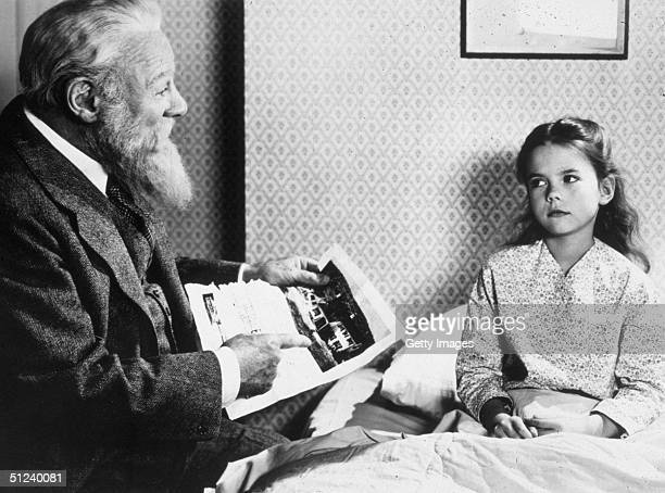 1947 Welsh actor Edmund Gwenn talks with American child actor Natalie Wood at her bedside in a still from director George Seaton's film 'Miracle on...