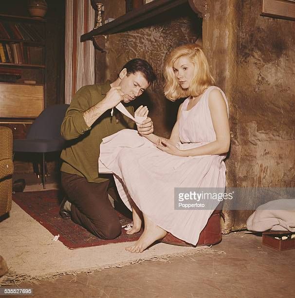 Welsh actor Peter Halliday wraps a bandage around the hand of English actress Susan Hampshire during the shooting of a scene from the BBC television...