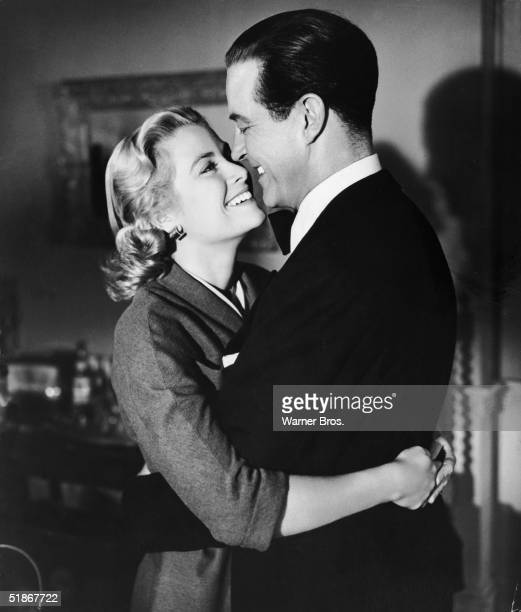 Welsh actor Ray Milland wears a tuxedo and hugs American actress Grace Kelly in a scene from 'Dial M for Murder' directed by Alfred Hitchcock and...