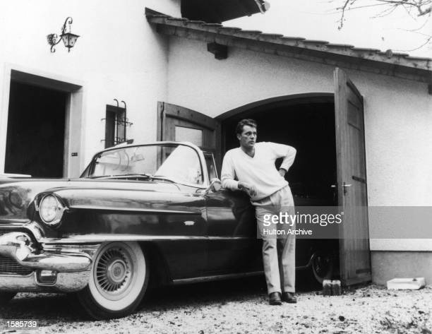 Welsh actor Richard Burton leaning on a Cadillac convertible circa 1955