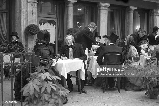 Welsh actor Richard Burton sitting at a table in St Mark Square during the shooting of the movie Wagner Venice 1983