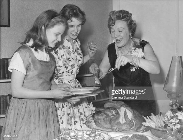 Welsh actress Doris Hare carves a turkey for her daughters Susan and Kathleen at a party at their home in Hampstead London 16th March 1959